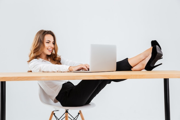 Felice giovane imprenditrice seduta e utilizzando il computer portatile con le gambe sul tavolo su sfondo bianco