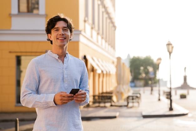Felice giovane uomo casual tenendo il telefono cellulare
