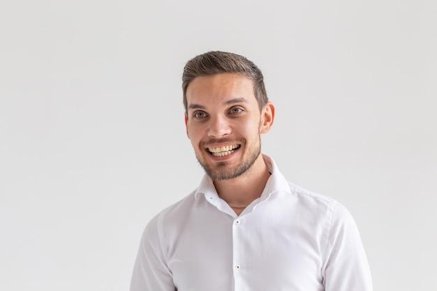 Ritratto di giovane uomo casual felice isolato sul muro bianco.