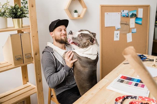 Felice giovane casual uomo seduto su una sedia da tavolo in legno e giocando con il suo cane di razza in pausa in ufficio a casa