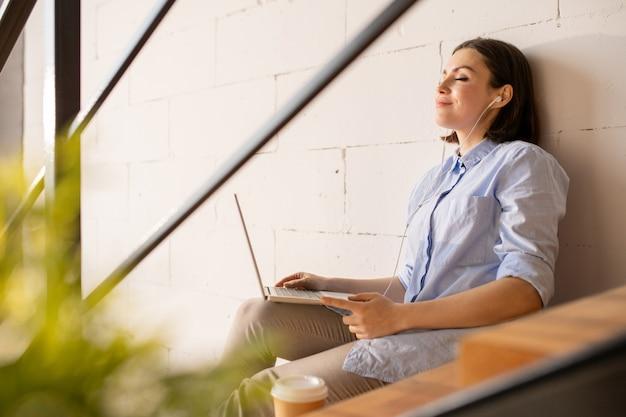 Felice giovane imprenditrice riposante casual con auricolari e laptop godendo la sua musica preferita mentre era seduto da parete