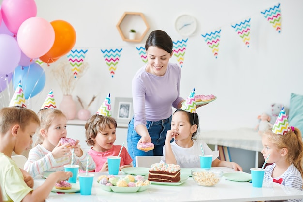 Felice giovane donna casual mettendo la ciambella sul tavolo servito mentre lo serve per la festa di compleanno per i bambini piccoli