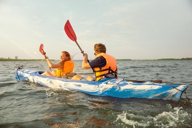 Felice giovane coppia caucasica in kayak sul fiume con il tramonto sullo sfondo. divertirsi in attività per il tempo libero. felice modello maschile e femminile che ride sul kayak. sport, concetto di relazioni. colorato.