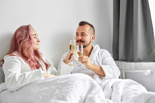 Felice giovane coppia caucasica rilassante a letto, bevendo champagne frizzante dai bicchieri. festeggiare. fine settimana, riposo, relax
