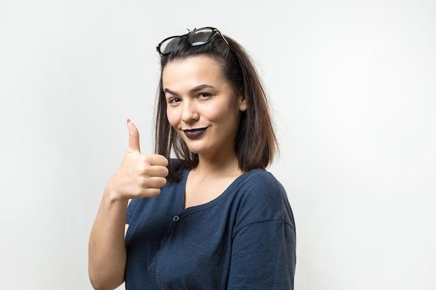 Felice giovane donna caucasica con gli occhiali e una maglietta blu che fa segno con il pollice e sorride
