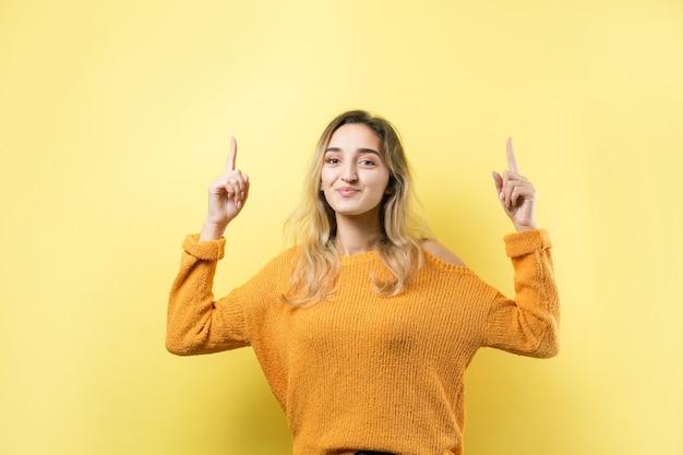 Felice giovane femmina caucasica in un maglione giallo che punta le dita lontano.