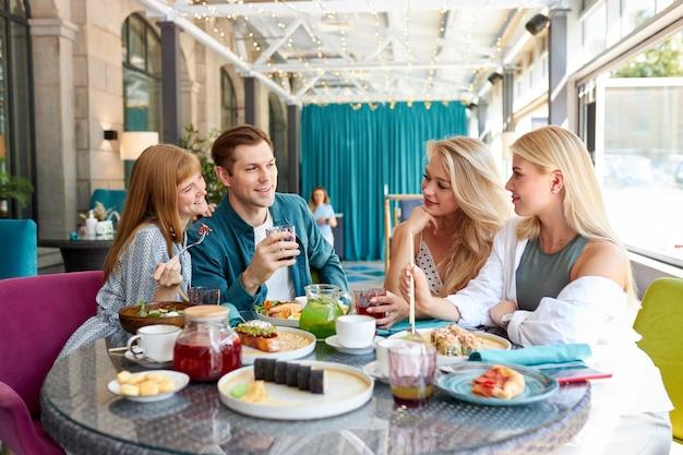 Giovani amici caucasici felici che si riuniscono nella caffetteria