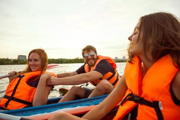 Felice giovane gruppo caucasico di amici in kayak sul fiume con il tramonto sullo sfondo. divertirsi in attività per il tempo libero. felice modello maschile e femminile che ride sul kayak. sport, concetto di relazioni. Foto Premium