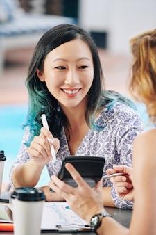 Felice giovane imprenditrice cinese guardando la calcolatrice con la somma del reddito mensile totale nelle mani del suo collega alla riunione
