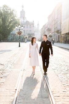 Felice giovane coppia cinese camminando per le strade del centro storico, in piedi sulla linea tranviaria.