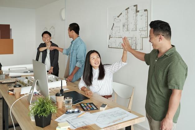 Giovani colleghi felici che fanno il gesto del cinque