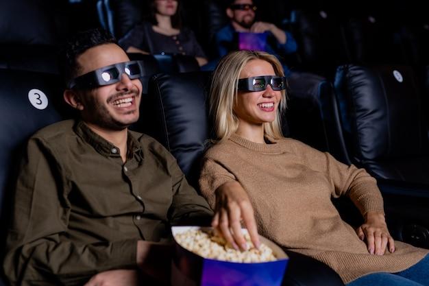 Giovani coppie felici in occhiali 3d che mangiano popcorn mentre si gode il tempo al cinema davanti al grande schermo