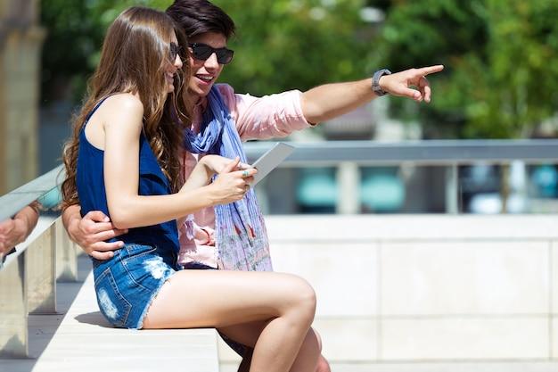 Giovani coppie felici che passano in rassegna internet con la compressa digitale nella via