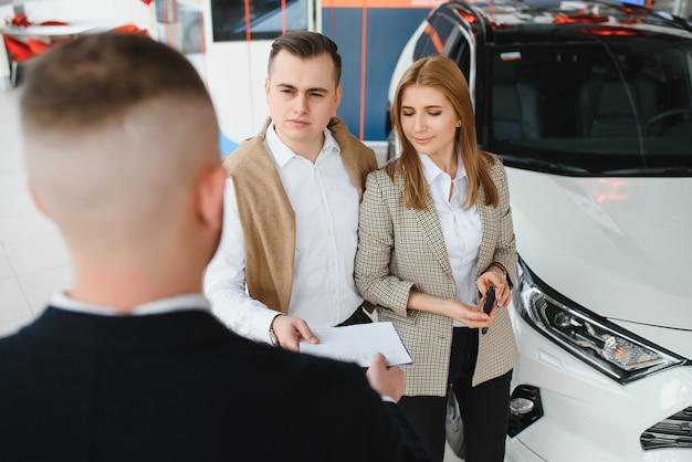 La giovane coppia felice sceglie e acquista una nuova auto per la famiglia nella concessionaria.