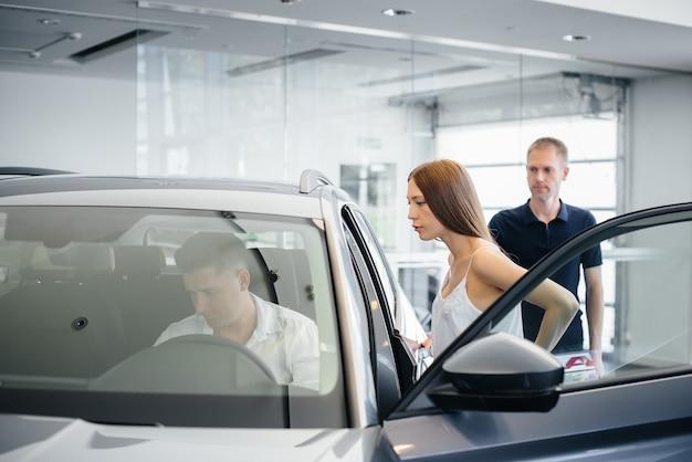 Una giovane coppia felice sceglie e acquista una nuova automobile presso una concessionaria di automobili. acquisto di un'auto nuova.
