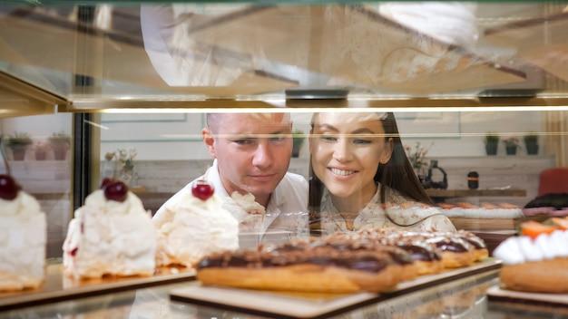 Una giovane coppia felice sceglie gustose torte fresche in piedi nella vetrina di una vetrina di una pasticceria vista ravvicinata