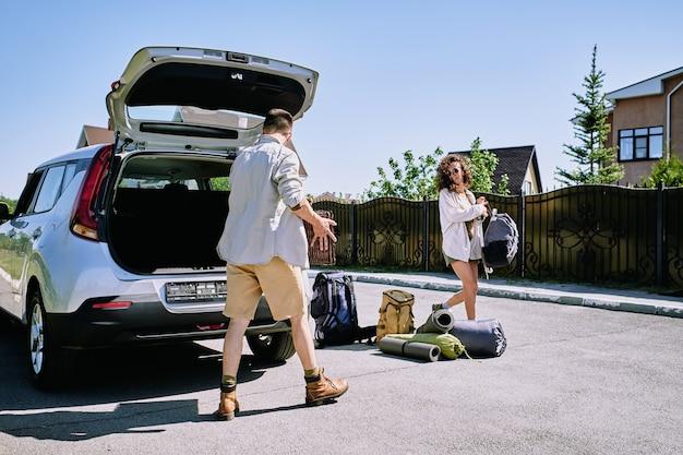 Giovani coppie felici che raccolgono i bagagli con i bagagli nel bagagliaio della macchina nella soleggiata mattina d'estate mentre viaggiano da soli nel fine settimana