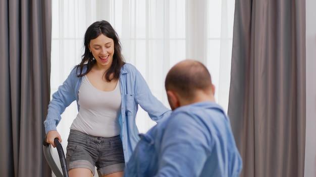 Felice giovane coppia che balla mentre pulisce la casa