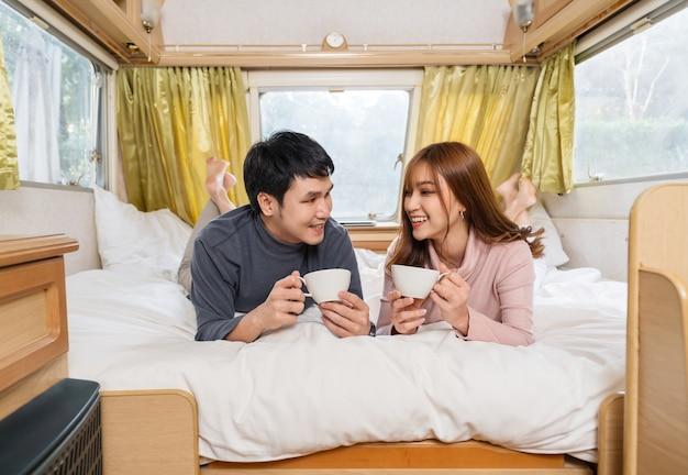 Giovani coppie felici che bevono caffè nel letto di un camper rv van motorhome