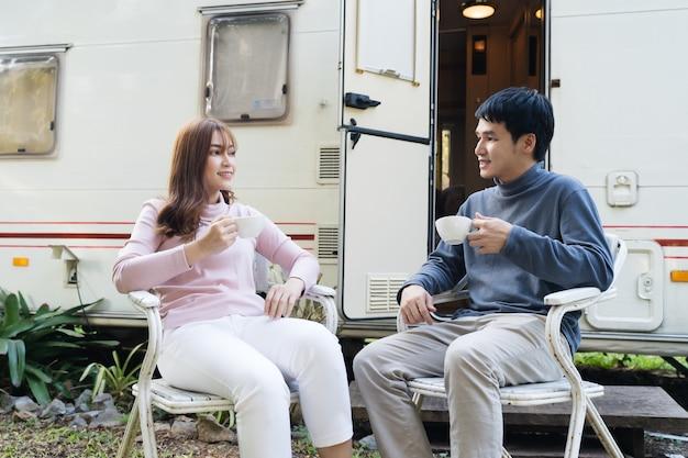 Giovani coppie felici che bevono caffè davanti a un camper camper van camper