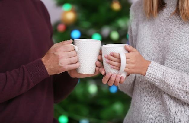 Giovani coppie felici che bevono cioccolata calda a casa. concetto di natale