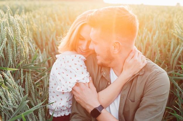 Abbracci di giovane coppia felice, seduti nell'erba alta in campo nei raggi del sole estivo al tramonto. amore e tenerezza. bei momenti di vita. giovinezza e bellezza. pace e disattenzione.