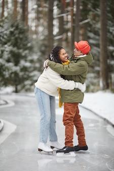 Giovani coppie felici che si abbracciano in piedi sulla pista di pattinaggio all'aperto in inverno