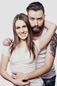 Felice coppia giovane abbracciando e guardando la fotocamera su bianco