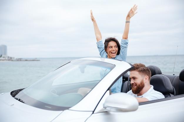 Giovani coppie felici che godono del viaggio su strada nella loro decappottabile bianca