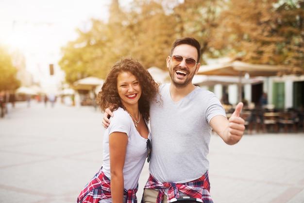 Le giovani coppie felici che godono dell'estate camminano nella città che esamina la macchina fotografica con un grande sorriso.