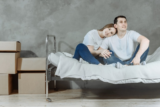 Donna e uomo di famiglia giovane coppia felice sono seduti sul letto che si abbracciano il giorno del trasloco nel soggiorno con scatole di cartone