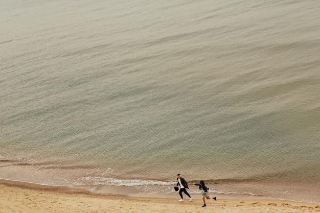 La giovane coppia felice si diverte sulla spiaggia. coppia romantica in esecuzione sulla spiaggia.