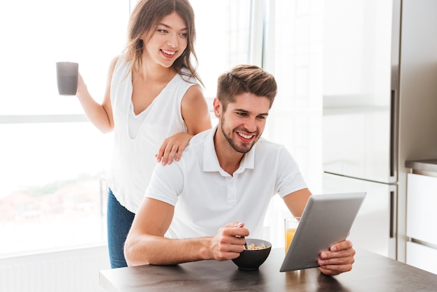 Felice giovane coppia che fa colazione e usa il tablet in cucina