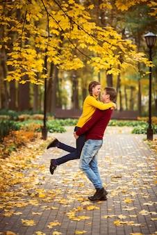 Giovani coppie felici che hanno divertimento e passeggiate nel parco in autunno