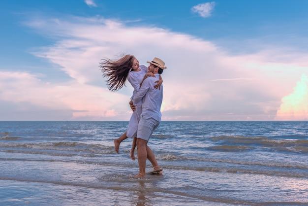 Giovani coppie felici che si tengono e che ridono con il godimento insieme sulla spiaggia di estate