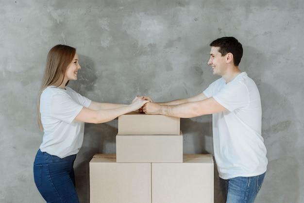 Giovani coppie felici che tengono le mani nella nuova casa