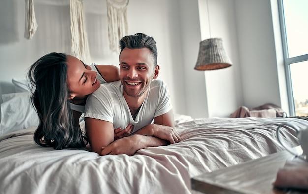 Felice giovane coppia che abbraccia e sorride mentre è seduto sul letto in una camera da letto a casa.