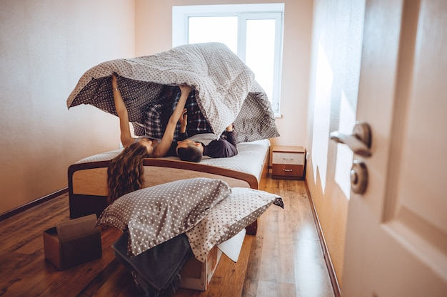 Felice giovane coppia si diverte a letto in una nuova casa vuota appassionata bella coppia che trascorre del tempo