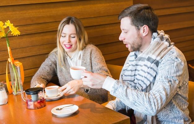 La giovane coppia felice sta parlando e bevendo caffè e sorridendo mentre sedendosi al caffè