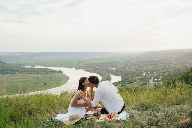 Giovani coppie felici che baciano e che hanno picnic all'aperto il giorno di estate.