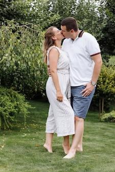 Giovani coppie felici che baciano e che abbracciano all'aperto il giorno di estate
