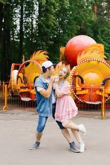 Giovani coppie felici nell'amore divertendosi in un parco di divertimenti e ballando