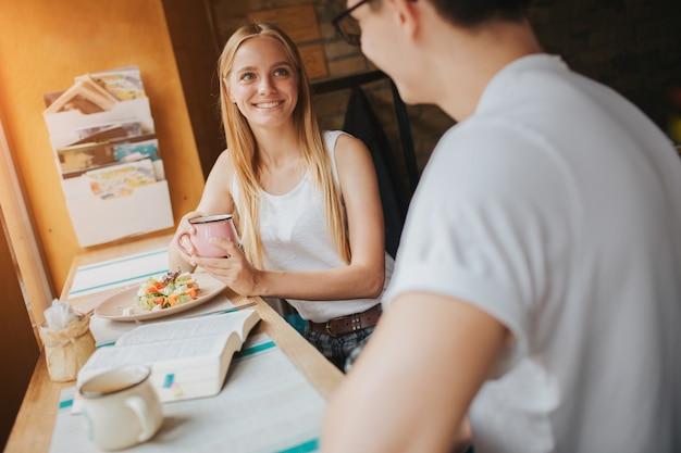 Giovani coppie felici nell'amore che hanno un bel appuntamento in un bar o in un ristorante