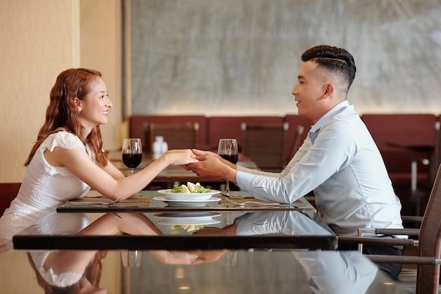 Felice giovane coppia innamorata seduta al tavolo del ristorante, tenendosi per mano e guardandosi negli occhi