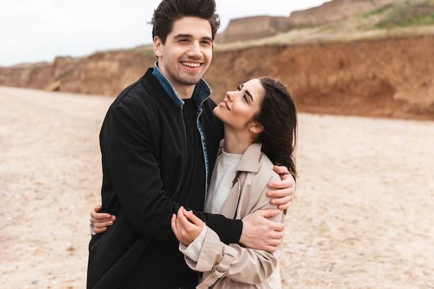Felice giovane coppia innamorata che indossa cappotti autunnali trascorrono del tempo insieme al mare, abbracciandosi