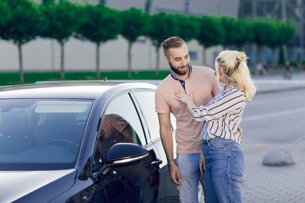 La giovane coppia, l'uomo e la donna felici ispezionano una nuova automobile. vendita di auto. acquisto di un'auto nuova.