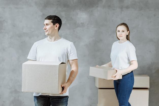 Felice giovane coppia uomo e donna con scatole per trasferirsi nella nuova casa