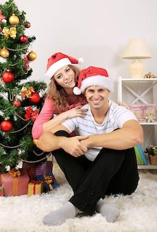 Felice giovane coppia vicino all'albero di natale a casa