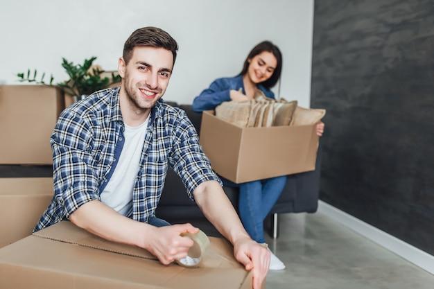 Felice coppia giovane imballaggio scatole di cartone durante il trasferimento