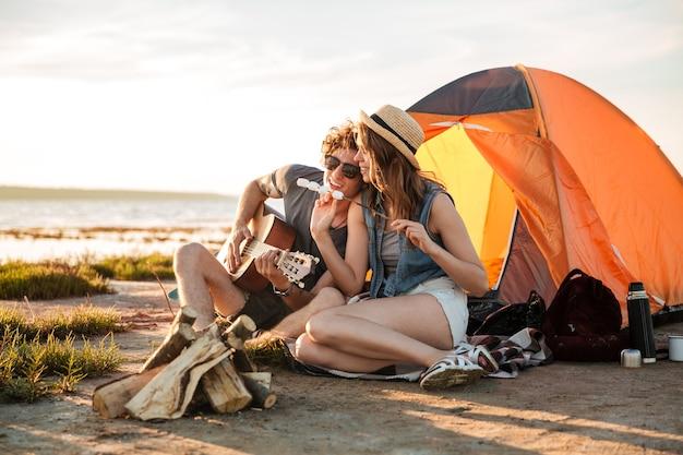 Giovani coppie felici che giocano chitarra e che mangiano marshmallow fritti vicino alla tenda turistica